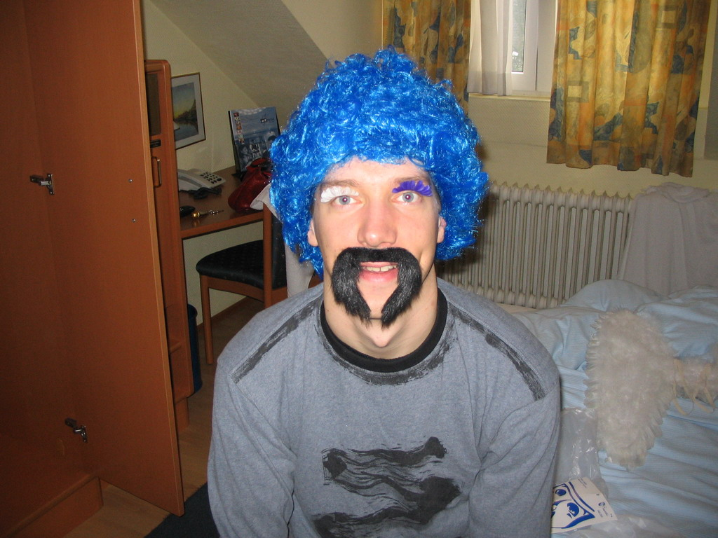 Tim with a wig, fake eyelashes and a fake mustache in our room at the Art Hotel Aachen