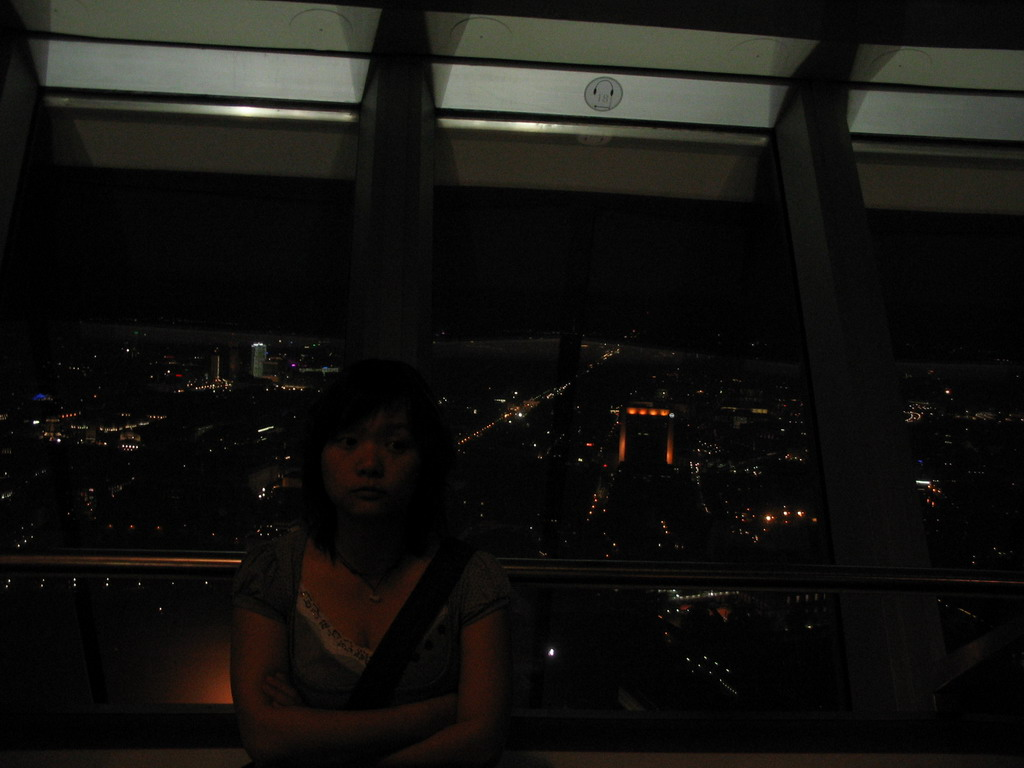 Miaomiao at the viewing point on top of the Fernsehturm tower, with a view on the west side of the city, by night