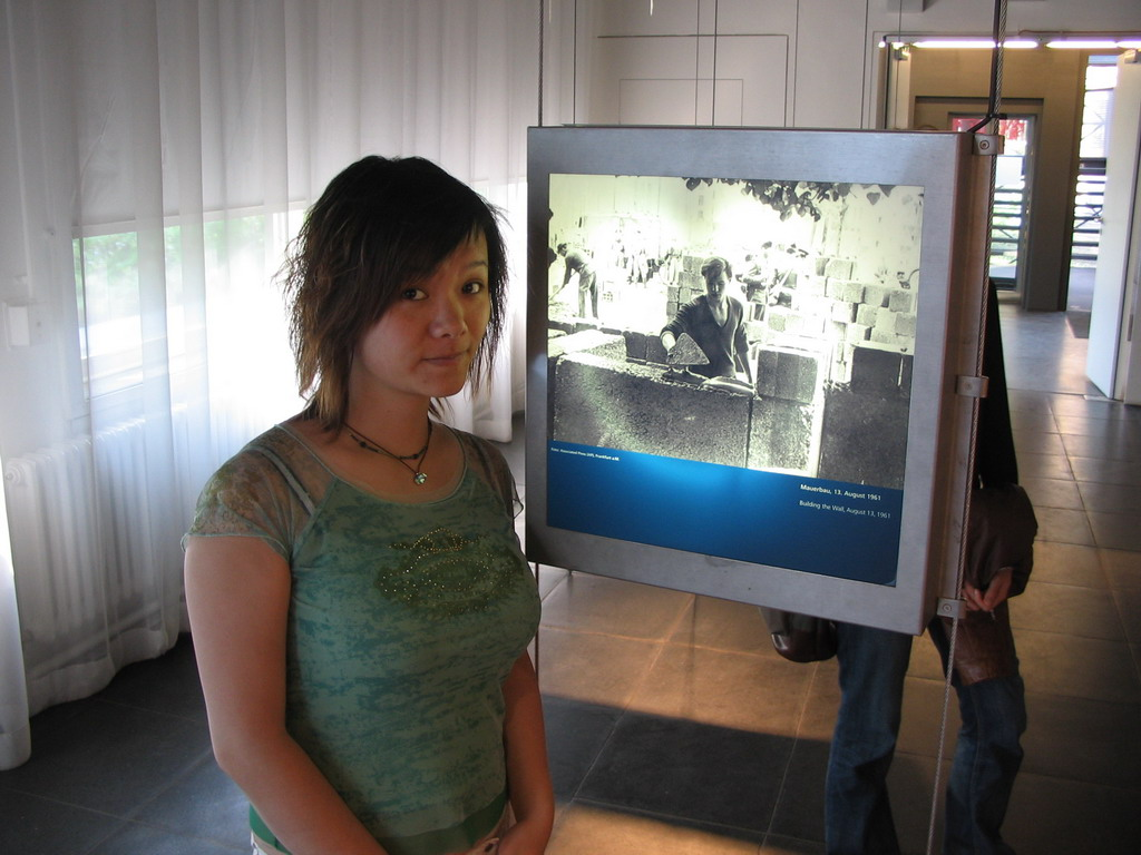 Miaomiao with a photograph of someone building the Berlin Wall, at the Gedenkst�tte Berliner Mauer museum