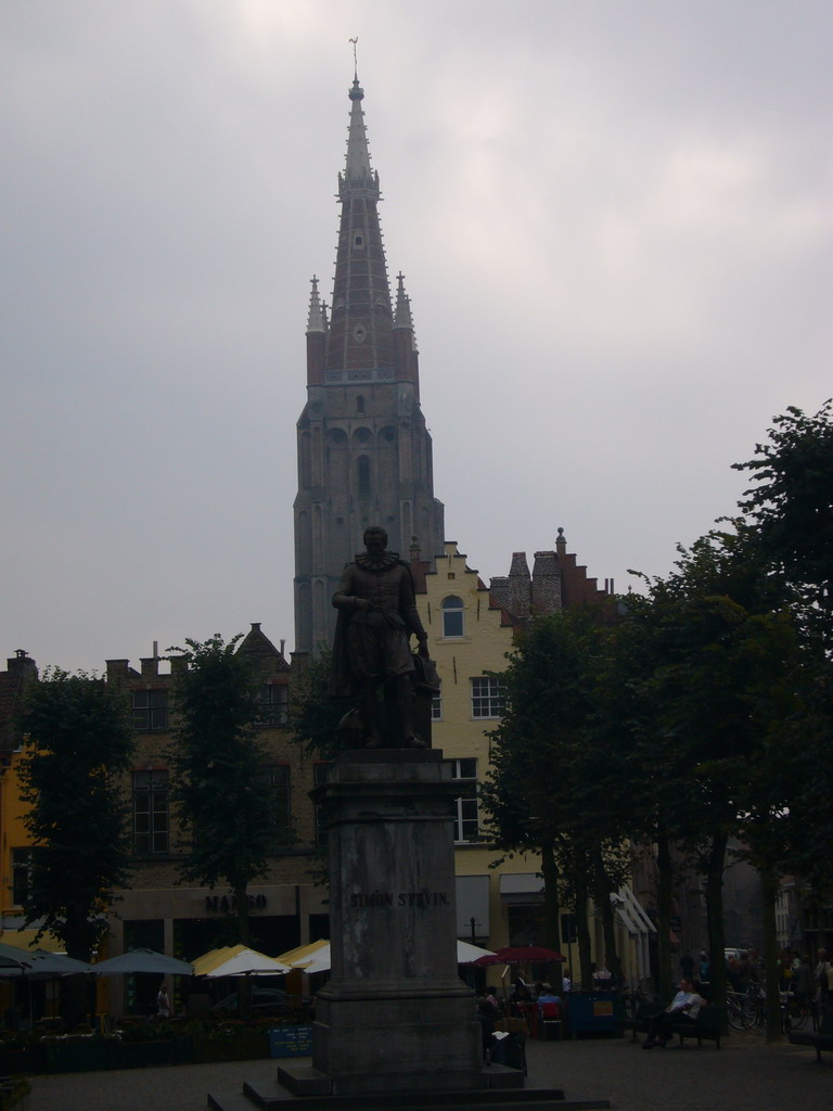 Statue of Simon Stevin at the Simon Stevinplein square, and the tower of the Church of Our Lady