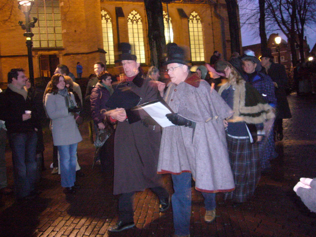 Actors in Victorian clothing in front of the St. Nicholas Church at the Bergkerkplein square, during the Dickens Festival parade, by night