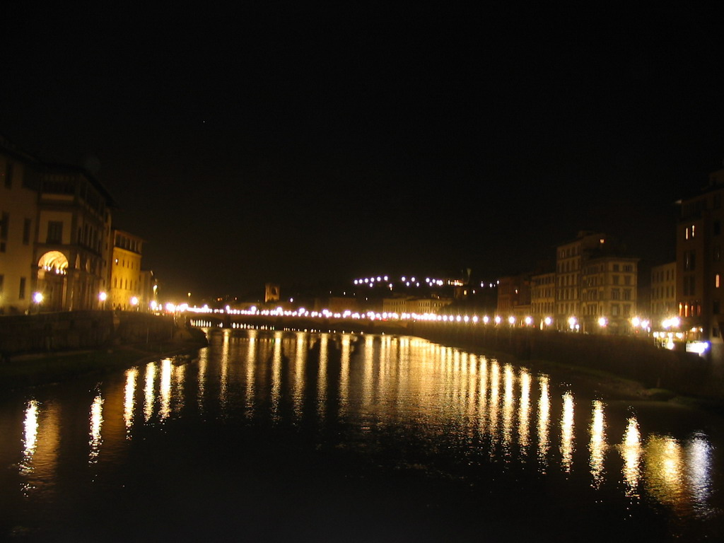 The Ponte alle Grazie bridge over the Arno river, viewed from the Ponte Vecchio bridge, by night