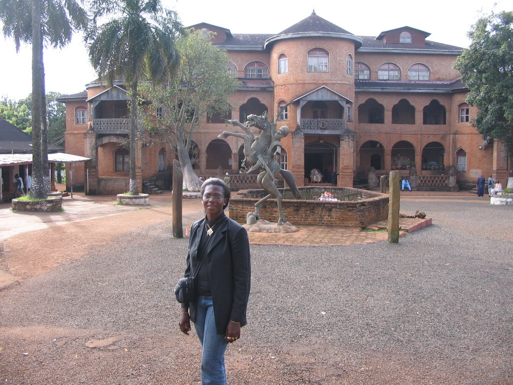 Our friend and a statue in front of the Foumban Royal Palace
