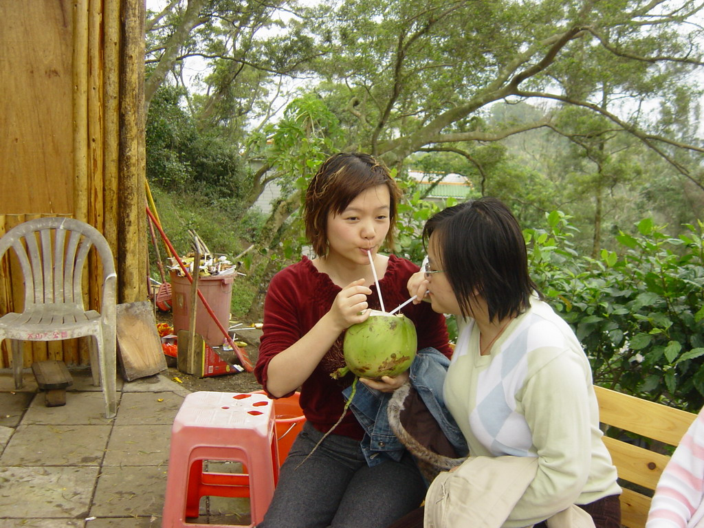 Miaomiao and her sister drinking from a coconut at the Mt. Fengluling volcano crater at the Hainan Volcano Park