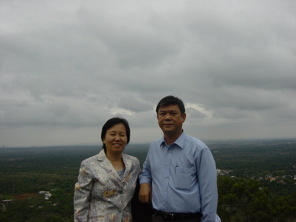 Miaomiao`s parents at the top of the Mt. Fengluling volcano crater at the Hainan Volcano Park, with a view on the surrounding area