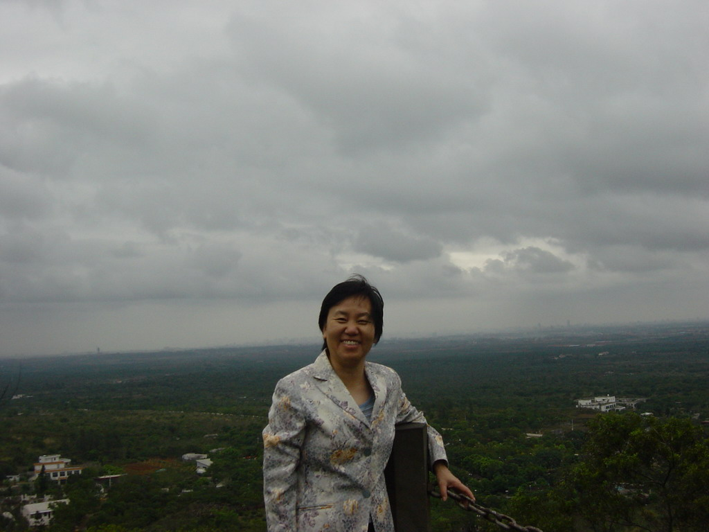 Miaomiao`s mother at the top of the Mt. Fengluling volcano crater at the Hainan Volcano Park, with a view on the surrounding area