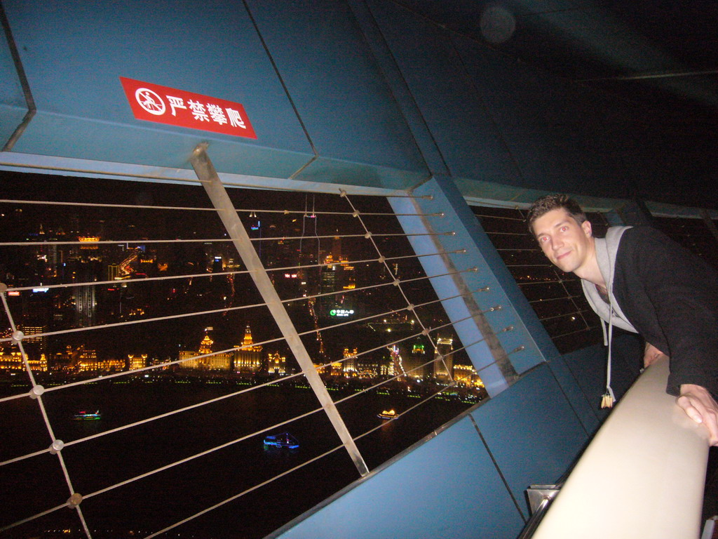 Tim at the top of the Oriental Pearl Tower, with a view on the Puxi skyline and the Bund area, with the Bund Center, Tomorrow Square and Le Royal M�ridien Shanghai, by night