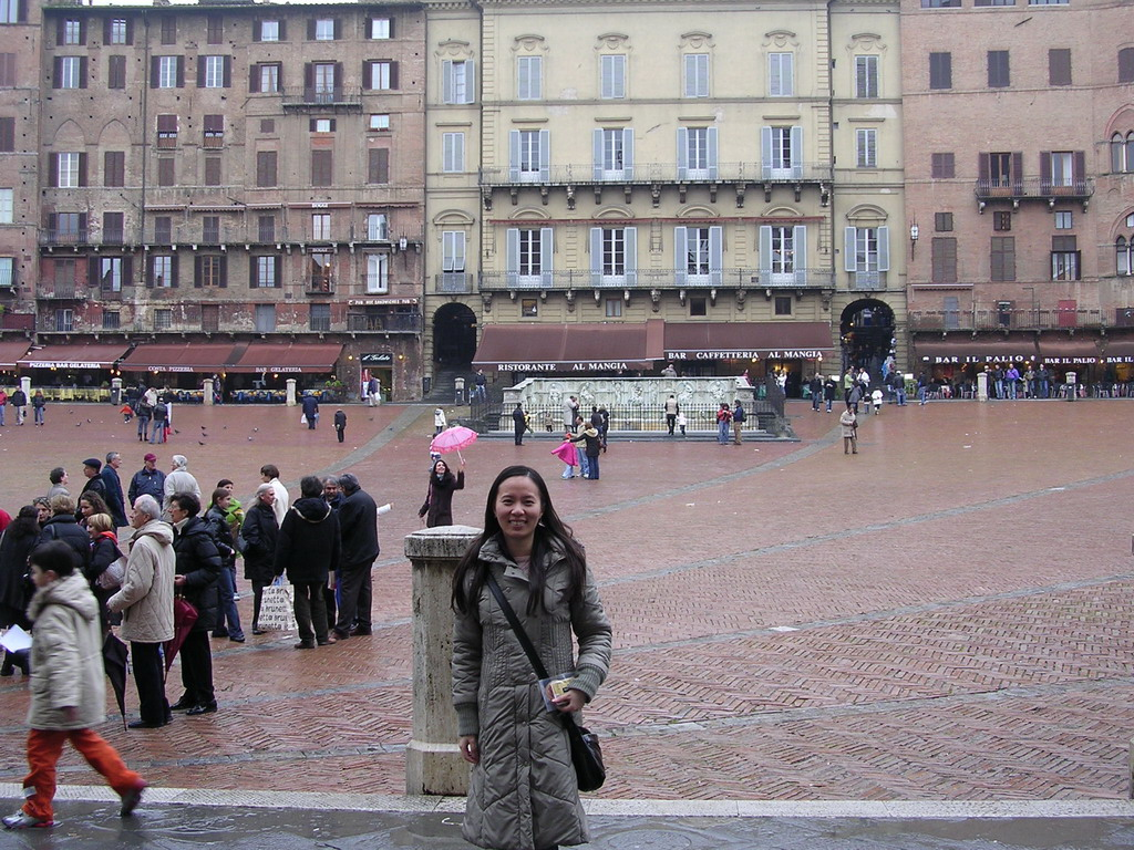 Miaomiao`s friend in front of the Gaia Fountain and the Loggia della Mercanzia building at the Piazza del Campo square