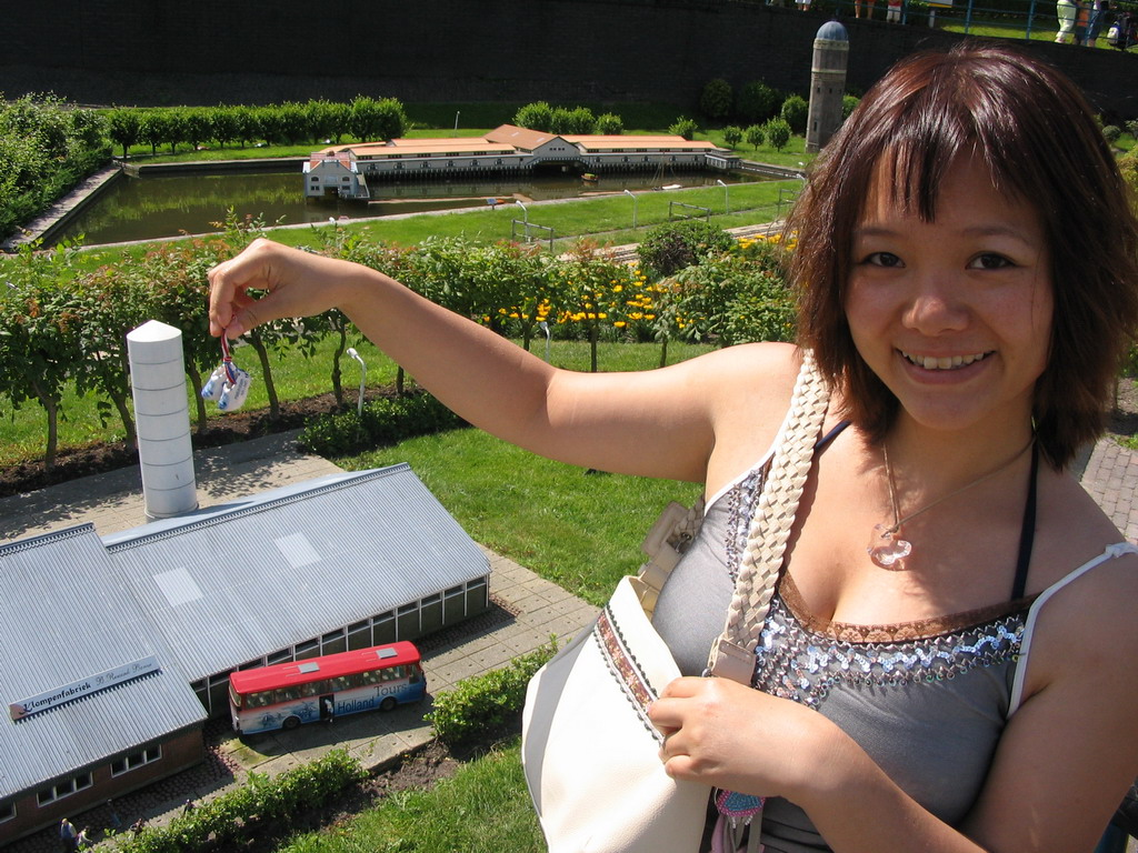 Miaomiao with miniature clogs in front of a scale model of the Klompenfabriek B. Roesink of Borne at the Madurodam miniature park